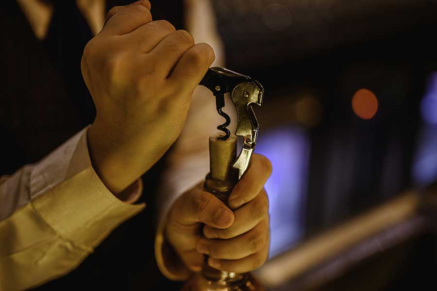 Opening wine bottle with a corkscrew.